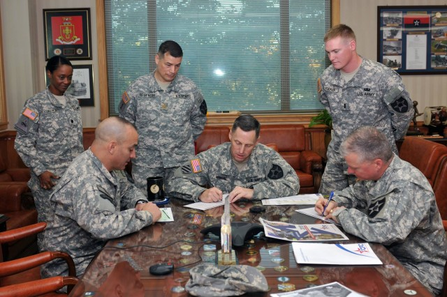 (right) First Lt. Leonard Weschler of Headquarters and Headquarters Battalion, 2nd Infantry Division looks on as the division's top three give their support. (Seated left to right)Division Command Sergeant Major, Command Sgt. Maj. Andrew Spano, 2ID Commander, Maj. Gen. Thomas S. Vandal, and division Chief of Staff Col. Marshall Dougherty makes a pledge to the 2013 Combined Federal Campaign in his office in Freeman Hall, the division's headquarters building, Oct. 16.