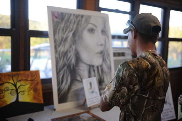 "An individual admires Christina Taylor's ""Elisha"" drawing during the Taste of the Arts Naturally 2013 art show held Thursday evening at the Piney Valley Golf Course. The event, hosted by Family and Morale, Wellness and Recreation, showcased various arts and crafts from local artists. This drawing by Taylor won honorable mention in the Army-wide competition held in August. Also on display was her drawing ""Azteca"" which placed 3rd in that same competition."