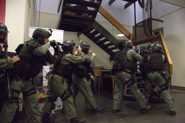 Law enforcement proceed through the heaquarters building of the Armament Research, Development and Engineering Center during the exercise.