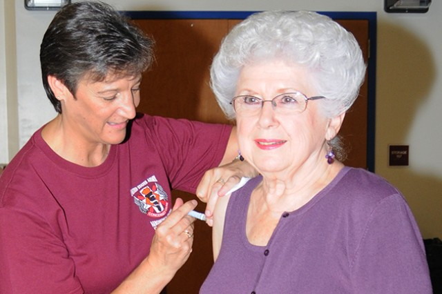 Mary Rutkowski, retired military, receives a flu shot from Jan Pridgen, allergy immunization nurse at Lyster Army Health Clinic, during last year's Retiree Health and Information Fair. This year's event is Oct. 25.