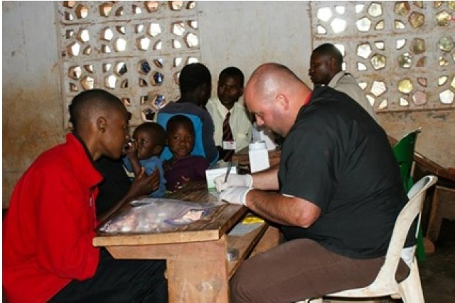 Jason Scarborough, right, conducts an initial consult on an incoming patient to the Muzgola Village Clinic during a mission trip to Malawi, Africa, in September.