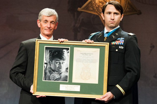 Secretary of the Army John McHugh presents Medal of Honor recipient former Capt. William D. Swenson with a photo and citation during Swenson's Induction Ceremony into the Hall of Heroes, at the Pentagon, Oct. 16, 2013. Swenson received the Medal of Honor for risking his life and going above and beyond the call of duty while serving as an embedded advisor to the Afghan National Border Police, Task Force Phoenix, Combined Security Transition Command-Afghanistan in support of 1st Battalion, 32nd Infantry Regiment, 3rd Brigade Combat team, 10th Mountain Division (Light Infantry), during combat operations against an armed enemy in Kunar Province, Afghanistan, on Sept. 8, 2009.