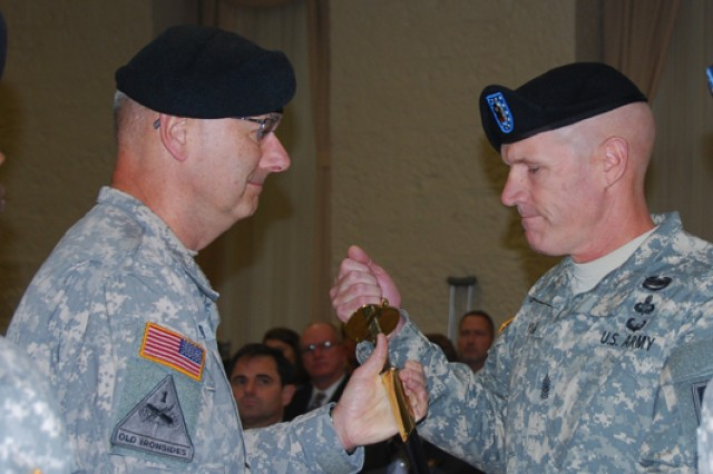 Command Sgt. Maj. Sam Young, right, receives the sword from Lt. Gen. Michael Tucker, First Army commander, which officially recognized him as the new First Army senior enlisted leader during a change of responsibility ceremony held Friday at the Rock Island Arsenal's Heritage Hall.