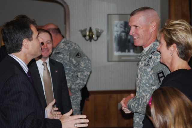 East Moline, Illinois Mayor John Thodos and Moline, Illinois Mayor Scott Raes, left, welcome Command Sgt. Maj. Sam Young and his wife Rhonda and daughter Chelsea to the Quad Cities following the change of responsibility ceremony held Friday at the Rock Island Arsenal's Heritage Hall.