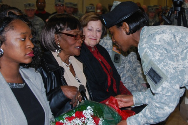 Sgt. 1st Class Leslie Ceasor presents a bouquet of red roses to Hattie Murray, mother of outgoing First Army Command Sgt. Maj. Jesse Andrews, during a Change of Responsibility ceremony Friday in Heritage Hall on Rock Island Arsenal. Andrews relinquished responsibility to Command Sgt. Maj. Sam Young.