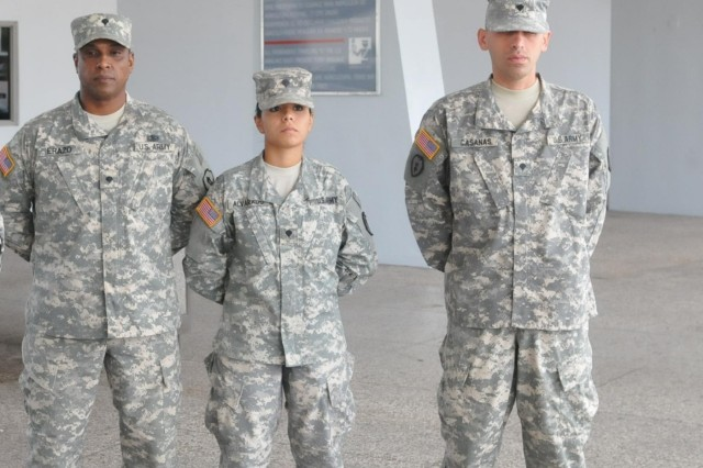 From left to right, Spc. Norberto Erazo-Calderon, Spc. Michelle Alvarado and Spc. Delimiro Casanas de Jesus pose for a photo minutes before their departure from Puerto Rico as part of a mobilization in support of the Defense Logistic Agency, Oct. 18, 2013.