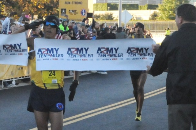 Solonei Silva from Washington DC bursts the finish line tape for first place at this year's U.S. Army Military District of Washington's Ten-Miler Race Oct 20, beginning and ending next to the Pentagon.