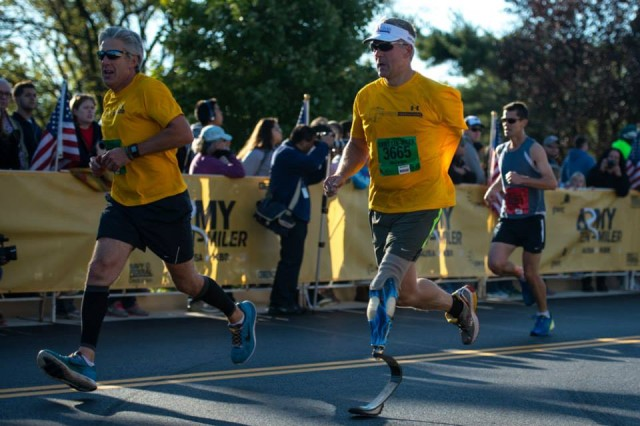 A wounded warrior finishes the 29th Army Ten-Miler with his running partner at the Pentagon, Oct. 20, 2013.