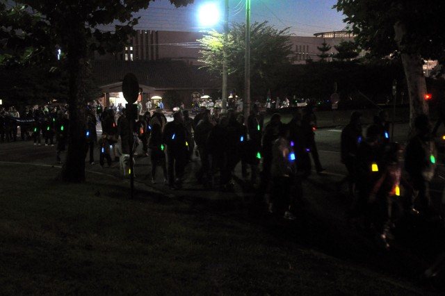 The attendees of the Take Back the Night event hold glow sticks and walk from Collier Field to Commiskey's Activity Center, here, Oct 16. Take Back the Night was created to increase awareness of domestic violence and also to strengthen the community. (U.S. Army photo by Pfc. Jung Young Ho)