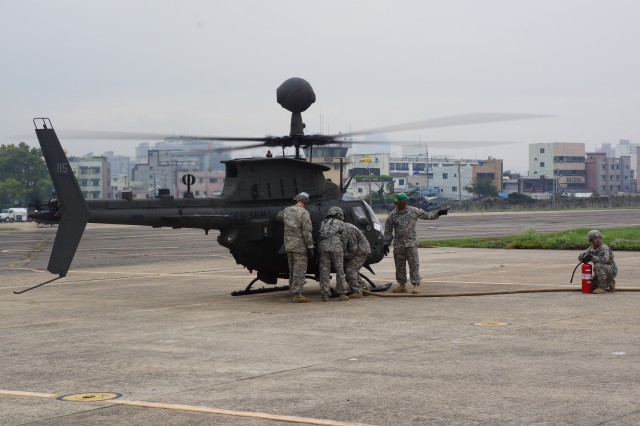 "CAMP HUMPHREYS, South Korea "" Soldiers from Company A, 602nd Aviation Support Battalion, 2nd Combat Aviation Brigade, perform a ""hot"" refuel on the new 4th Attack Reconnaissance Squadron, 6th Cavalry Regiment OH-58 Kiowa Warrior helicopters at Camp Walker Oct. 10, 2013."