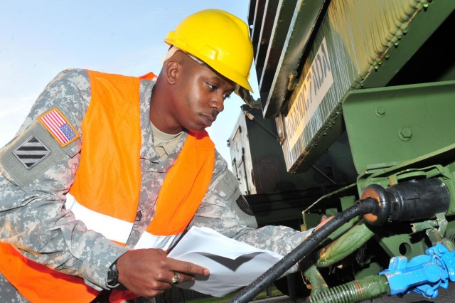 Staff Sgt. Tyler P. Jackson, the transportation movement and installation staging area supervisor with the 21st Theater Sustainment Command and a native of Queens, N.Y., inspects a vehicle belonging to the 5th Battalion, 7th Air Defense Artillery at Rhine Ordnance Barracks Oct. 18.