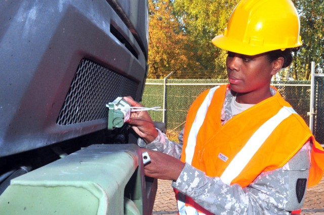 Sgt. 1st Class Kimberlie S. Harris, the staff movment noncommissioned officer with the 21st Theater Sustainment Command and a native of Albany, Ga., ensures a tracking beacon is properly attached to a vehicle at Rhine Ordnance Barracks Oct. 18.