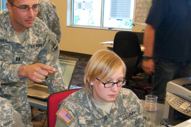 Capt. Chris Meyer, Army Space Support Team operations officer, 117th Space Battalion left, gives guidance to Pvt. Miranda Yost, geospatial engineer, on the type of products Colorado civilian authorities need during the Colorado floods in September.