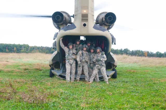 Pilots and crew from B Company, 6th Battalion, 101st Combat Aviation Brigade, 101st Airborne Division (Air Assault), pose in front of the tail gate of a CH-47 Chinook helicopter after flying Pathfinders from F Company, 5-101st CAB, on their final jump at Fort Campbell, Ky., Oct. 16, 2013. The dedication and willingness of the pilots and crew to fly in inclement weather allowed the Pathfinders to complete this historic jump.