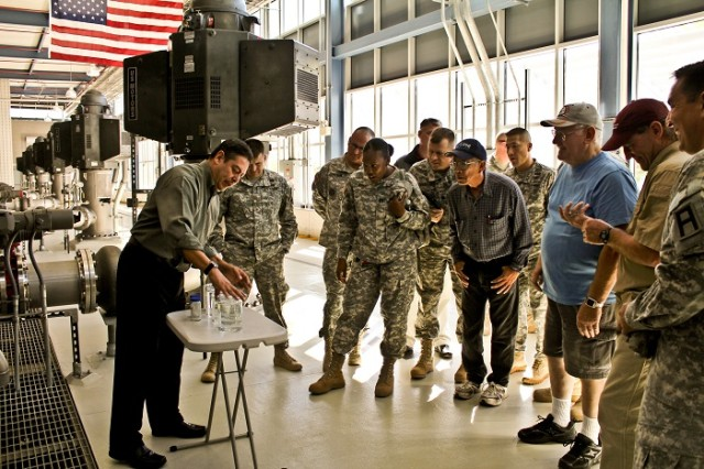 Civilians with the El Paso Society of American Military Engineers Post and uniformed members of the 5th Armored Brigade, 1st Armored Division, the William Beaumont Army Medical Center, and Joint Task Force North watch as Art Ruiz, superintendent of the Kay Bailey Hutchison Desalination Plant, explains how much salt is in the water when it first comes to the plant in comparison with how much is left once the process of reverse osmosis is complete in El Paso, Texas, recently. Tour attendees were allowed to sample the salty water as well as the fresh water that is pumped out to El Paso, Texas. (Photo by 1st Lt. Vanessa Dudley, 1st Battalion, 361st Regiment, Task Force Redhawk, 5th Armored Brigade, Division West Public Affairs)