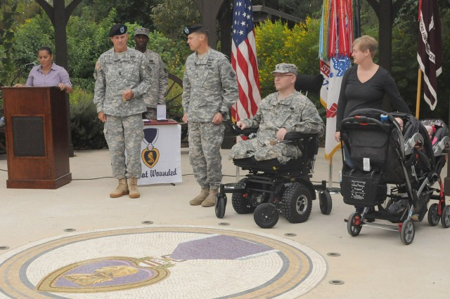 FORT SAM HOUSTON, Texas - Command Sgt. Maj. Hu Rhodes (left) and Maj. Gen. William Roy prepare to present the Purple Heart Medal to Staff Sgt. Edward Matayka during a ceremony Oct. 18 at the Warrior and Family Support Center. Matayka, a combat medic, served with Company A, Special Troops Battalion, 86th Infantry Brigade Combat Team, Vermont National Guard, when he was wounded in July 2010. The brigade was commanded by (then Col.) Roy, who now serves as deputy commanding general for U.S. Army North (Fifth Army). Rhodes is the senior enlisted leader for Army North, Fort Sam Houston and Camp Bullis. Also pictured are Matayka's wife, Karen, and their two children.