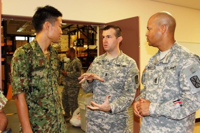 Army 1st Lt. Alexander Horton (center), the executive officer for the 349th Signal Company, 78th Signal Battalion, explains a piece of communications equipment to 1st Lt. Kazukyoshi Sugamura, a signal officer assigned to the 15th Brigade, Japan Ground Self Defense Force, as 1st Sgt. Dwight West (right), first sergeant assigned to  the 349th, looks on.  The 349th hosted about 20 Japanese soldiers during a bi-lateral event to help strengthen the relationship between American and Japanese soldiers.