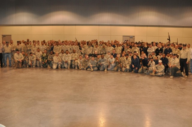 Soldiers from the 2d Brigade Combat Team, 1st Armored Division's 1/1 Cavalry, 1/6 Infantry, 1/35 Armor and the Special Troops Battalion who comprise the Red Team, or OPFOR, for NIE 14.1 pose with their instructors from the TRADOC Wargaming, Experimentation, Test and Evaluation Directorate (on the far left and far right) and the chief of the Brigade Modernization Command's Threat Support section, Col. Jay Popejoy (second from the left), who is assigned to the TRADOC G-2 Intelligence Support Activity.