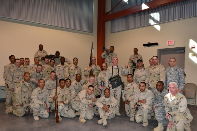 A group of 2/1 AD OPFOR soldiers pose with the weapons they will be using during the upcoming NIE 14.1. Standing in the back row, far right, is Col. Jay Popejoy, chief, BMC Threat Support section, TRADOC G-2 Intelligence Support Activity. Kneeling in the front row, second from the right is Lt. Col. Lawrence White, who is assigned as the OPFOR commander and commander of the Special Troops Battalion, 2/1 AD. Next to him, far right, is the OPFOR Operations Officer Maj. Eric Morton.