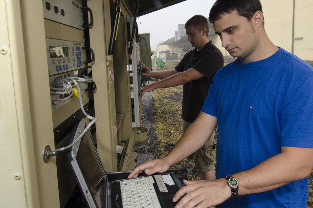 Integrated Systems Electronic Mechanics Adam Wojcicki (left) and Chris Sicurella run systems tests on the AN/TSC-185 Satellite Transportable Terminal at Tobyhanna Army Depot.