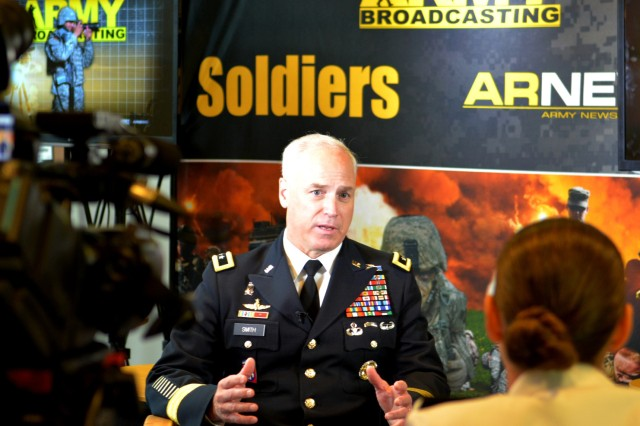 Maj. Gen. Jefforey Smith, commander of the U.S. Army Cadet Command, explains changes for the ROTC program to Army broadcaster Sgt. Rachel Badgeley at the 2013 Association of the United States Army Annual Meeting and Exposition, Oct. 22, 2013, at the Washington (D.C.) Convention Center.