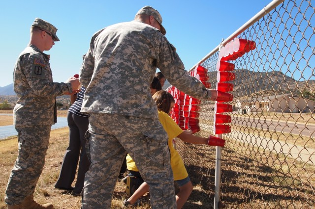"From left, Sgt. Jonathan Russas and Staff Sgt. Randy Roscoe, Headquarters and Headquarters Company, U.S. Army Garrison, help General Myer Elementary School students decorate the school's fence to read, ""A Healthy Me is Drug Free!"" on Oct. 18. Students involved in the project are peer mediators, meaning they receive training on conflict resolution skills and they help manage conflict between students on the playground."