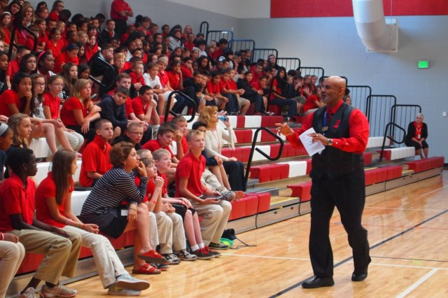 Kevin Mills, Army Substance Abuse Program manager, engages with Colonel Smith Middle School students during Monday's Red Ribbon Week Proclamation Ceremony. Ditching the podium, Mills came up to the bleachers to make students active listeners and participants.