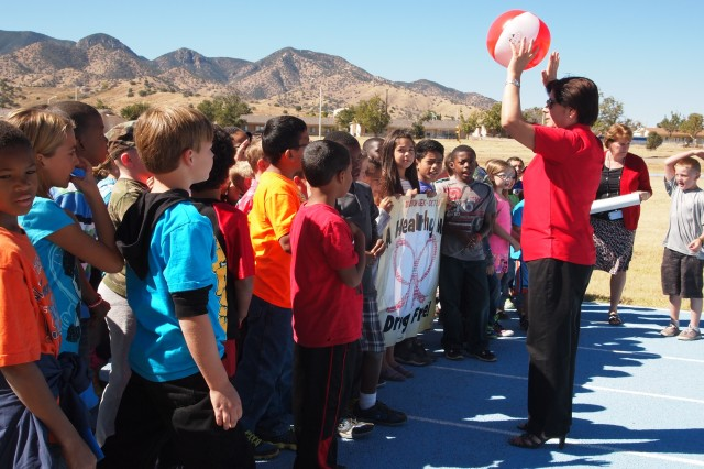 "From right, Rosa Peralta-Imamura Army Substance Abuse Program prevention coordinator, talks to third grade students at General Myer Elementary about the Drug Free Pledge before their Red Ribbon run/walk during lunch recess Monday. Other Red Ribbon Week activities included a poetry contest and wearing different themed clothing each day, such as wearing a tie today to support the theme, ""don't get tied down with drugs."""
