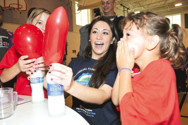 Rachael Fine (center), Marymount University student, reacts with Shyla Goff (left), 9, and Tamara Alden (right), 5, as their balloons fill with air when baking soda and vinegar mix in the attached water bottles during the Fort Belvoir Elementary School STEM Family Day event Saturday.