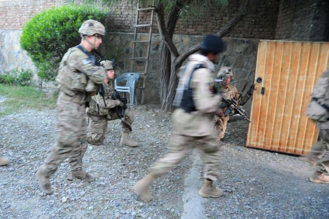 Soldiers from Easy Company, 2nd Battalion, 506th Infantry Regiment, 4th Brigade Combat Team, 101st Airborne Division (Air Assault), exit from a compound during a partnered patrol in Madi Khel, Khowst Province, Afghanistan, Oct. 20, 2013. The Soldiers conducted a partnered operation with the newly formed Khowst Provincial Response Company. The operation was used to validate the training that the Khwost PRC recently received and ensure that illegal weapons were not being stored in historical weapons cahce points.