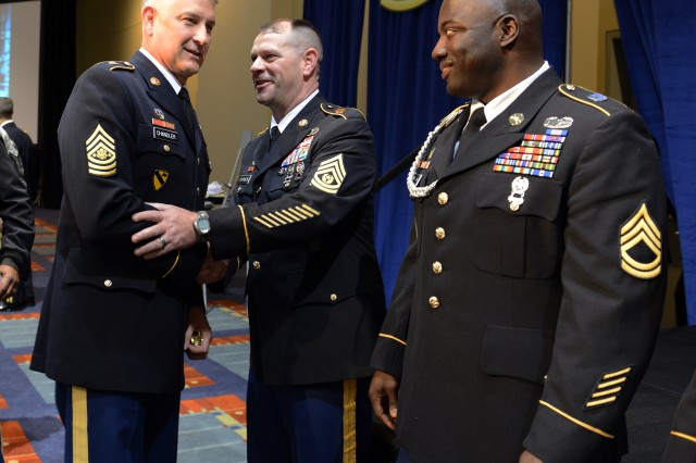 Sgt. Maj. of the Army Raymond F. Chandler III greets the recipients of the Larry Strickland Educational Award, Command Sgt. Maj. Ronald Johnson of Joint Base Lewis-McChord, Wash. (center); and Sgt. 1st Class Rodney Harris of Fort McCoy, Wis., at the Association of the United States Army Annual Meeting and Exposition, in Washington, D.C., Oct. 21, 2013.