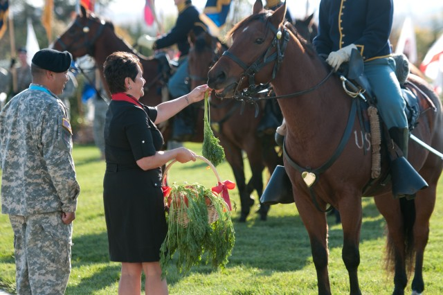 Frances Sasser, wife of Command Sgt. Maj. Charles V. Sasser Jr., former senior noncommissioned officer, 1st Inf. Div., feeds a customary carrot to one of the Commanding General's Mounted Color Guard mounts during a ceremony Oct. 25, at Fort Riley's Victory Park. During the ceremony, those from the 1st Inf. Div., Fort Riley and Flint Hills region of Kansas said goodbye to the Sassers and welcomed Command Sgt. Maj. Michael A. Grinston as the division's 23rd senior noncommissioned officer.