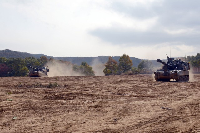 Two M109A6 Paladin 155-mm Self-Propelled Howitzers drive through the field at Rooster 8 Training Area as they assume their firing positions during the Combined Top Gun Competition on Oct 24, 2013. The combined competition included the Republic of Korea Army 7th Field Artillery Brigade, 661st Field Artillery Battalion,  which is the sister unit of U.S. 1st Battalion, 15th Field Artillery Regiment, 1st Armored Brigade Combat Team, 2nd Infantry Division. (U.S. Army photo by Cpl. Kwon Yong-joon, 1ABCT PAO)