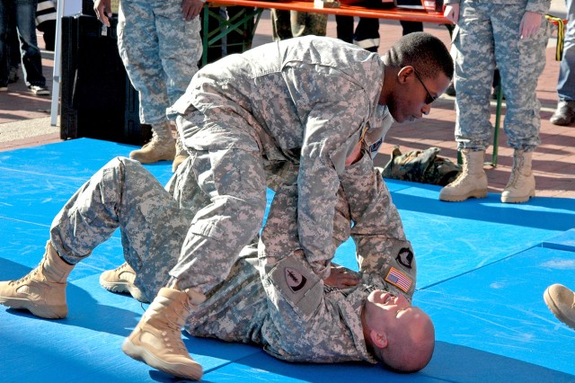 Spc. Brooks Turner and Sgt. Sean Hall demonstrate aspects of Army combatives to Bundeswehr reservists and citizens of Fulda Sept. 28 during the 2013 Day of the Reservists event.
