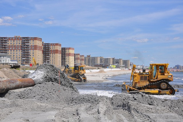 A sand and water slurry mixture pumps onto Rockaway Beach on August 15, 2013 as part of beach renourishment efforts there. The angle shows the severely eroded areas where sand will be placed next as well as some of the densely populated areas where the sand being placed will help to reduce risk from future storms. Post-Sandy sand placement activities are underway at Rockaway Beach in Queens, NY as part of a project placing roughly 3.5 million cubic yards onto the beach to help reduce risks from future storms. (Photo by New York District, public affairs)