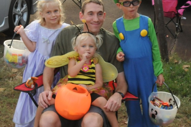 Maj. Joseph Foust, intelligence officer for 311th Signal Command (Theater), poses for a picture with his family during the HHC/516th Signal Brigade Trunk-or-Treat here on 25 Oct.