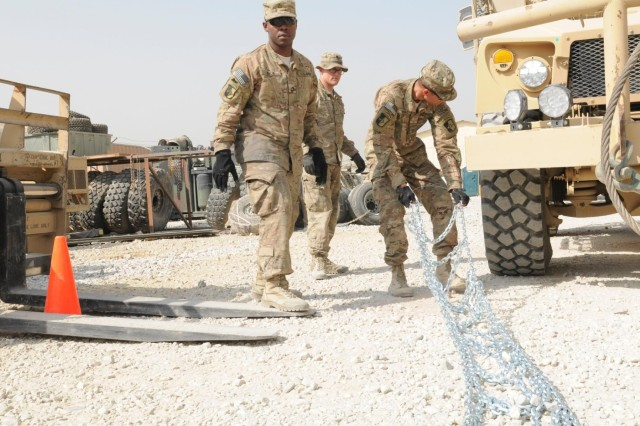 Pfc. Ryan M. Sindle (right), a native of Elkhart, Ind., with the command security team, drags a snow chain toward a mine-resistant ambush-protected vehicle tire, during winter training class, Oct. 26, 2013, at Bagram Airfield in Parwan province, Afghanistan. Pfc. Val J. Irick (left), a native of Daytona Beach, Fla., and a driver with the CST, moves to help Sindle with the placement of the chain, while Spc. Victor W. Stephans (center) a native of Clarksville, Tenn., and instructor, observes the Soldiers' performance. All three Soldiers are with the Task Force Lifeliner. This training teaches the Soldiers how to properly apply snow chains on tires and how to operate their vehicles in cold weather conditions.