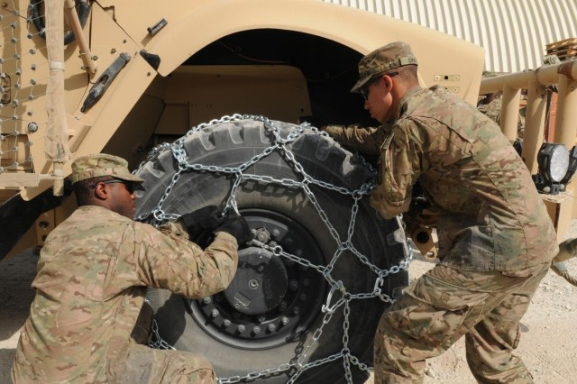Pfc. Val J. Irick (left), a native of Daytona Beach, Fla., and Pfc. Ryan M. Sindle (right), a native of Elkhart, Ind., both Soldiers with the Task Force Lifeliner command security team, attach firmly a snow chain on a mine-resistant ambush-protected vehicle tire as part of winter training class, Oct. 26, 2013, at Bagram Airfield in Parwan province, Afghanistan. This training teaches the Soldiers how to properly apply snow chains on tires and how to operate their vehicles in cold weather conditions.