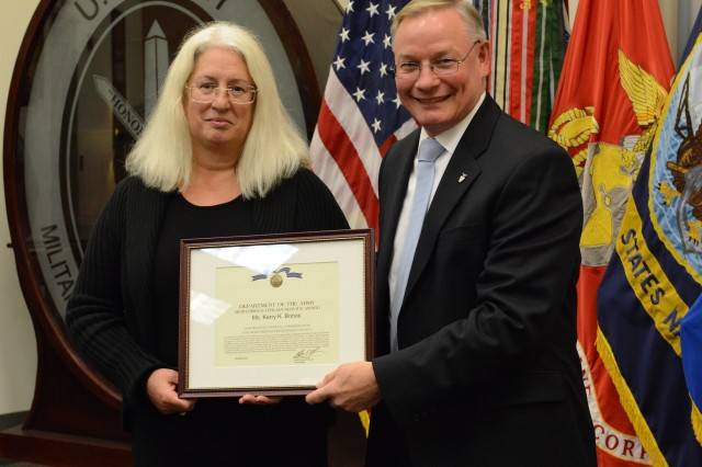 Mr. Egon F. Hawrylak, Joint Force Headquarters-National Capital Region/U.S. Army Military District of Washington deputy commander, presents the Meritorious Civilian Service Award to Ms. Kerry K. Bonos during her retirement awards ceremony held at Fort Lesley J. McNair, 28 October.