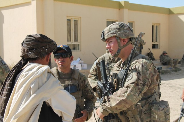 First Lt. Michael Shepard, a Miami native and a platoon leader with Troop A, 6th Squadron, 8th Cavalry Regiment, 4th Infantry Brigade Combat Team, 3rd Infantry Division, speaks with the headmaster of a local school, Sept. 23, 2013, in Logar Province, Afghanistan. The 6-8 Cav. Soldiers delivered school supplies in order to support educational development and foster good relations with the Afghan citizens.