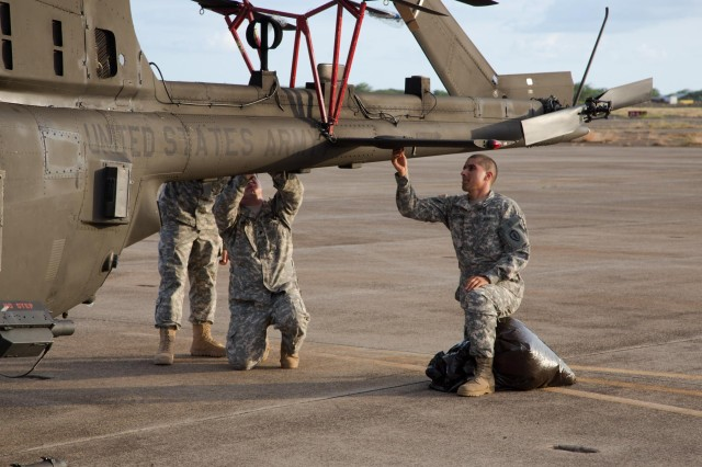 Soldiers from 2nd Squadron, 6th Cavalry Regiment, 25th Combat Aviation Brigade, 25th Infantry Division, prep an OH-58D Kiowa Warrior to be loaded onto a C-17 Globemaster III during a Contingency Response Force validation exercise Oct. 21. (Photo by Chief Warrant Officer 3 Mark Leung, 2nd Squadron, 6th Cavalry Regiment)