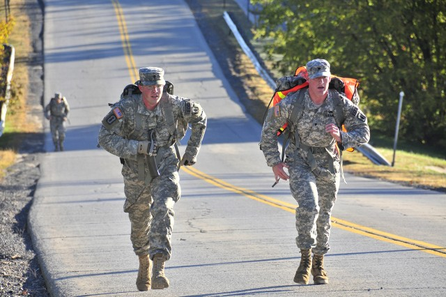 Spc. Michael Fletcher and Spc. Kevin Ray, both team members assigned to 725th Explosive Ordnance Disposal Company, push themselves up the last hill of the ruck march Oct. 9. Each badge had a designated distance requirement for the Soldiers to ruck.
