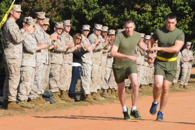 FORT GORDON, Ga., (Oct. 29, 2013) - Lance Cpl. Caleb Kempf, the first runner in the ninth annual  United States Marine Corps Tribute to the Fallen Run, hands off the ammo pouch carrying 21 rounds of ammo to Staff Sgt. Timothy Gernand of Company D, Marine Cryptologic Support Battalion, the second runner in the tribute Oct. 29 on Barton Field.
