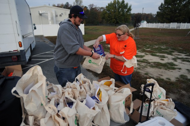 Lucas Catlett (left) and Judy Collins (right) of USAG Fort A.P. Hill Family and Morale, Welfare and Recreation prepare goodie bags for all runners and walkers who finished the annual Halloween 5-Kilometer Run and Walk.