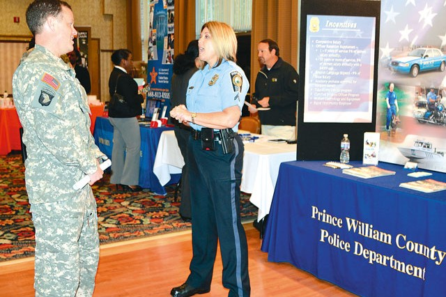 CWO2 Mark Layne, Bravo Company, 12th Aviation Battalion, left, speaks with Officer Sherrie Farley, Prince William County Police Department, Police Recruiter, right, during Fort Belvoir's Installation Job Fair at the Community Center, Oct. 24.