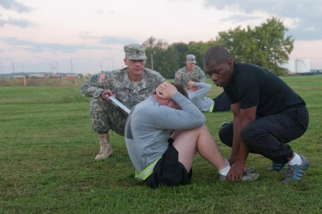 Sgt. Frans Vandiepenhuisen, C Company, 5th Battalion, 101st Combat Aviation Brigade, 101st Airborne Division (Air Assault,) UH-60 Black Hawk crew chief performs the situps while Sgt. 1st Class Jimmie Jones, F Company, 2nd Squadron, 17th Cavalry Regiment, platoon sergeant holds his feet and Sgt. 1st Class Paul Goeman, Headquarters and Headquarters Company, 101st CAB, operations noncommissioned officer grades the event ensuring all repetitions were conducted properly during an Army physical fitness test held at 101st CAB headquarters, Fort Campbell, Ky, Oct. 9, 2013. (U.S. Army photo by Sgt. Duncan Brennan, 101st CAB Public Affairs)