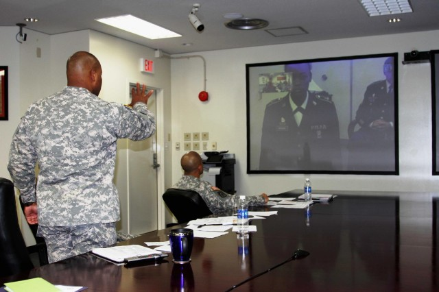 Command Sgt. Maj. Shelton R. Williamson, command sergeant major for the 10th Regional Support Group, gives instructions during the 10th RSG's Soldier and Noncommissioned Officer of the Year board via teleconference to Spc. Cintajia Spencer, a systems administrator assigned to the 35th Combat Sustainment Support Battalion, Oct. 25th at the unit's headquarters conference room on Torii Station, Okinawa, Japan. Spencer finished in second place as the Soldier of the Year.