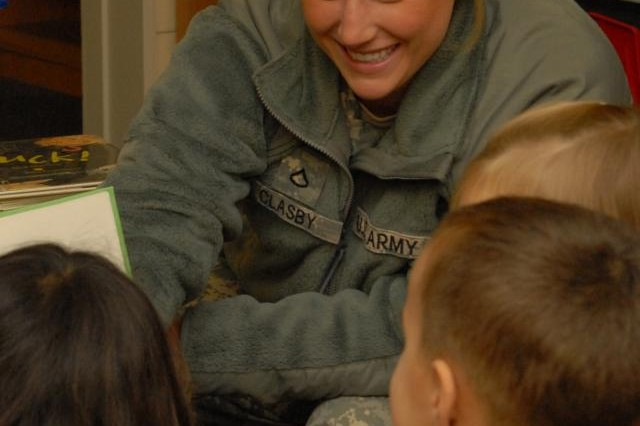 Pfc. Maria Clasby, a military police Soldier with 2nd Platoon, 529th Military Police Company, 95th Military Police Battalion, lets a group of children get a closer look as she shares a laugh with them at the Mannheim Library on Benjamin Franklin Village in Mannheim, Germany, during the weekly after school reading program sponsored by the platoon.