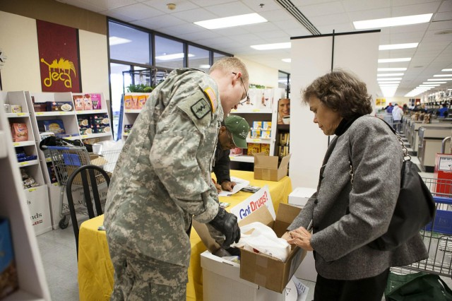 Andrew Rader U.S. Army Health Clinic pharmacy NCOIC Sgt. Stuart Arnett, left, and Army Substance Abuse Program Prevention Coordinator George Suber, center, collect items from Maggie Maguire during Drug Take-Back Day on Joint Base Myer-Henderson Hall in the commissary Oct. 25, 2013. JBM-HH collected 222 pounds of unused or expired medications.