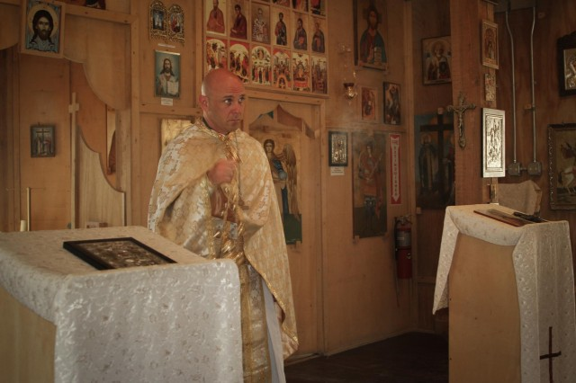 Maj. Ruston Hill, command chaplain for Combined Joint Special Operations Task Force - Afghanistan, fills St. Gheorghe Chapel on Kandahar Airfield, Afghanistan, with incense during an Orthodox Church service Oct. 13, 2013. (U.S. Army photo by Cpl. Mariah Best)